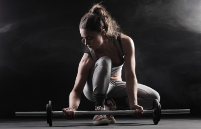 female athlete grabbing barbell