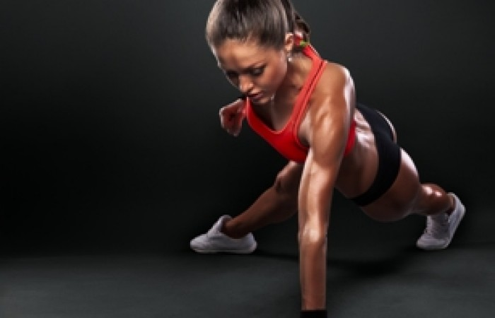 fit woman doing one arm push up