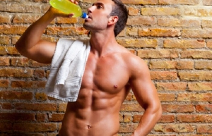 male physique competitor drinking sports drink