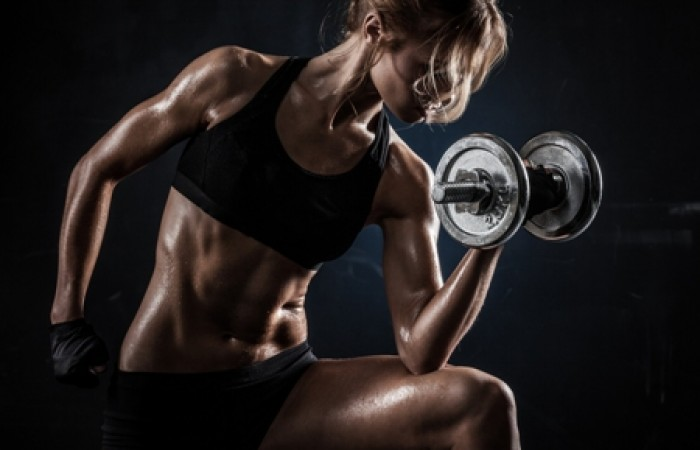 ripped lady doing dumbbell curls