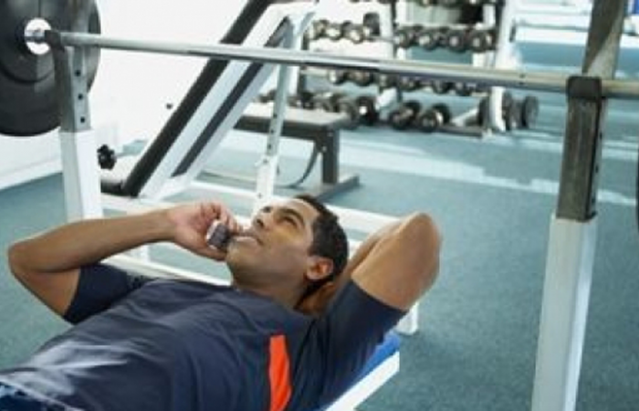 man with poor gym manners on bench press