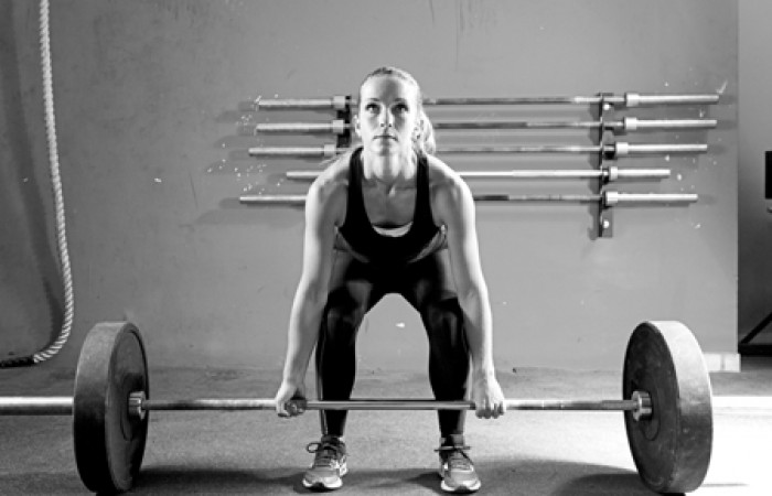 woman deadlifting to stimulate muscle fibers