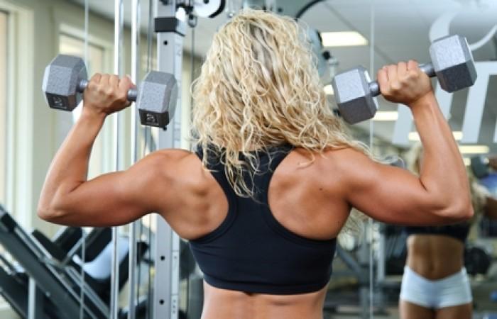 female bodybuilder doing dumbbell presses
