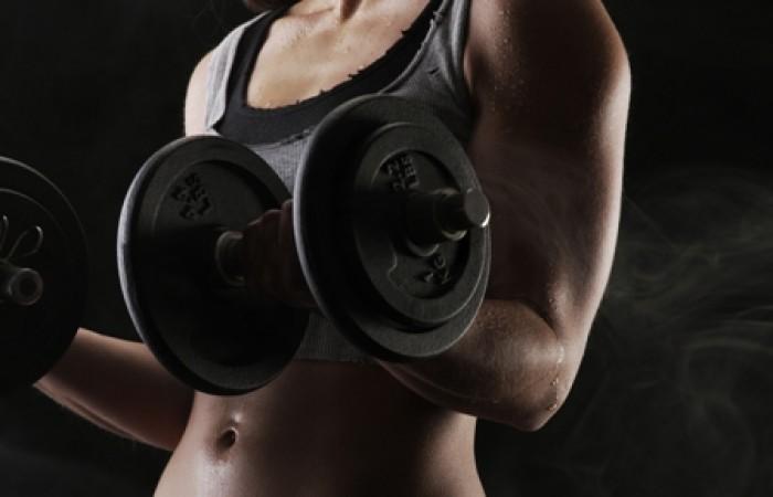 bodybuilder curling dumbbells